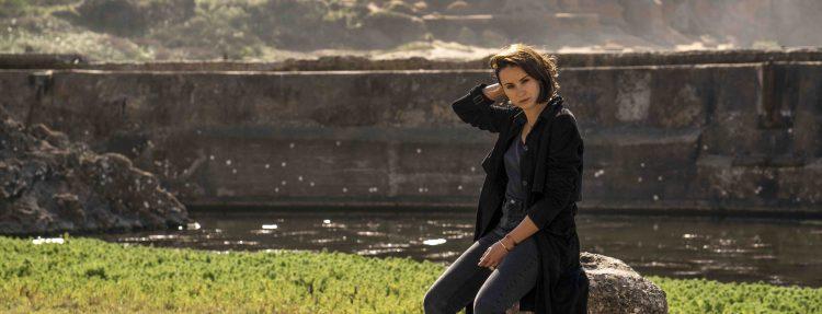Holly Miranda sitzt auf einer Mauer im Grünen.