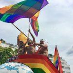 Drei Männer oben ohne auf dem CSD Truck 2016 die die Regenbogenfahne schwenken