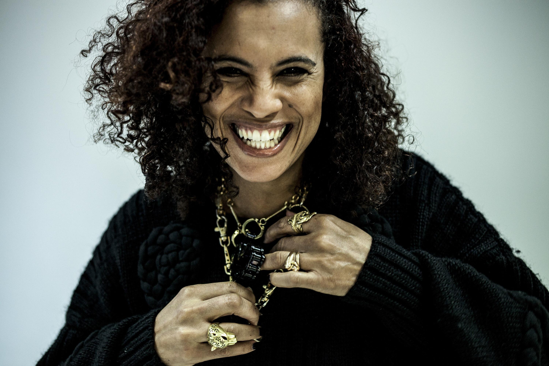 Neneh Cherry lacht in die Kamera. Sie trägt einen schwarzen Pullover und Goldschmuck.