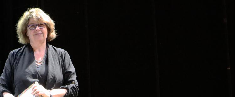 """Meg Wolitzer steht auf der dunklen Bühne und hält ihr Buch """"Das weibliche Prinzip"""" in den Händen."""