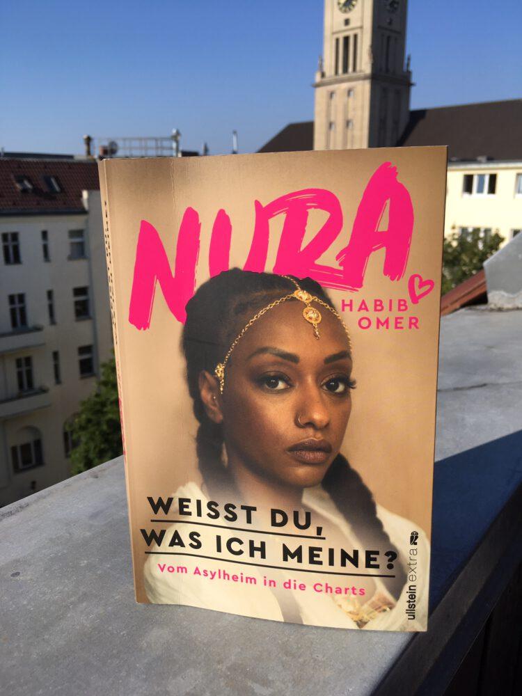 Zu sehen ist Nuras Buch Weisst du was ich meine auf dem Balkon in der Sonne