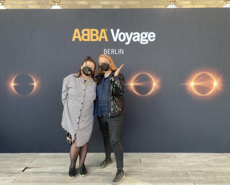 Olga und Nina vor der Abba Voyage Wand beim Event